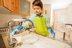 Garçon ouvrant le robinet et rinçant des plats dans l'évier Photo stock