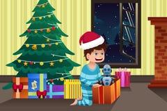 Garçon ouvrant un présent sous l'arbre de Noël Image stock