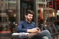 Garçon parlant avec l'amie par l'appel et l'earphon visuels de smartphone Image stock