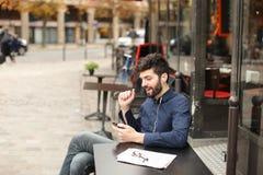 Garçon parlant avec l'amie par l'appel et l'earphon visuels de smartphone Image libre de droits