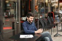 Garçon parlant avec l'amie par l'appel et l'earphon visuels de smartphone Photo stock