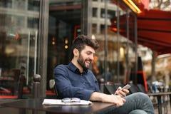 Garçon parlant avec l'amie par l'appel et l'earphon visuels de smartphone Photo libre de droits