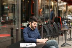Garçon parlant avec l'amie par l'appel et l'earphon visuels de smartphone Images libres de droits