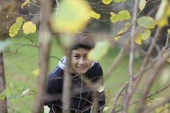 Garçon parmi les arbres Photo stock