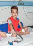 Garçon patient asiatique avec l'intravenous salin (iv). Photographie stock libre de droits