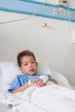 Garçon patient asiatique avec l'intravenous salin (iv). Photos libres de droits