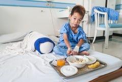 Garçon patient asiatique avec l'intravenous salin (iv) sur le lit d'hôpital. Photographie stock libre de droits