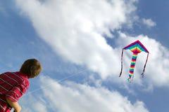 Garçon pilotant un cerf-volant. Images stock