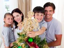Garçon plaçant une étoile de Noël sur le dessus d'un arbre Image libre de droits