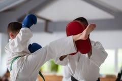 Garçon portant les gants protecteurs bleus ayant le combat avec l'entraîneur images libres de droits
