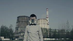 Garçon portant un respirateur contre des cheminées d'usine Concept de pollution atmosph?rique banque de vidéos