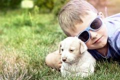 Garçon posant avec le petit chiot Photos libres de droits
