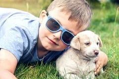 Garçon posant avec le petit chiot Photos stock