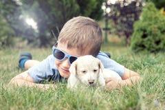 Garçon posant avec le petit chiot Photo libre de droits