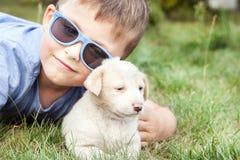 Garçon posant avec le petit chiot Photographie stock