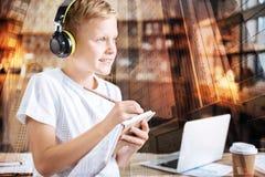 Garçon positif faisant remarquable tout en utilisant de grands écouteurs Images libres de droits