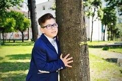 Garçon près d'arbre en stationnement Photo stock