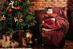 Garçon près d'un arbre de Noël Photographie stock