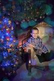 Garçon près de l'arbre de Noël Photo stock