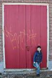 Garçon près de trappe en bois rouge image stock