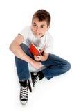 Garçon pré de l'adolescence s'asseyant avec un livre Image libre de droits