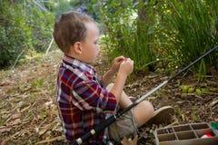 Garçon préparant une amorce dans la forêt Photo stock