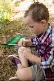 Garçon préparant une amorce dans la forêt Photos libres de droits