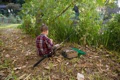 Garçon préparant une amorce dans la forêt Photo libre de droits