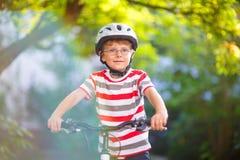 Garçon préscolaire d'enfant dans le casque ayant l'amusement avec l'équitation de la bicyclette Images stock