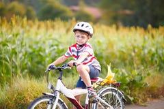 Garçon préscolaire d'enfant dans le casque ayant l'amusement avec l'équitation de la bicyclette Photos stock