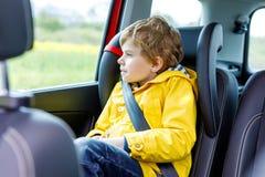 Garçon préscolaire mignon adorable d'enfant s'asseyant dans la voiture dans le manteau de pluie jaune photo stock