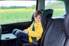 Garçon préscolaire mignon adorable d'enfant s'asseyant dans la voiture dans le manteau de pluie jaune photographie stock libre de droits