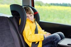 Garçon préscolaire mignon adorable d'enfant s'asseyant dans la voiture dans le manteau de pluie jaune Peu d'écolier dans le siège photographie stock