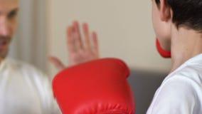 Garçon pratiquant enfermant dans une boîte des poinçons avec l'instructeur à l'école de sport, autodéfense clips vidéos