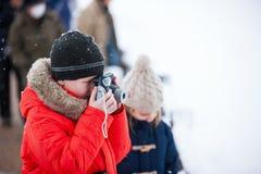 Garçon prenant des photos le jour d'hiver Photos stock