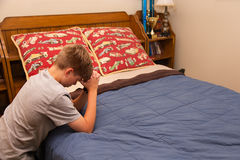 Garçon priant dans sa chambre à coucher Photographie stock