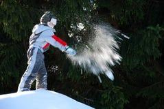 Garçon projetant une boule de neige Photographie stock libre de droits