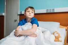 Garçon réfléchi d'Ittle s'asseyant sur le lit d'hôpital image stock