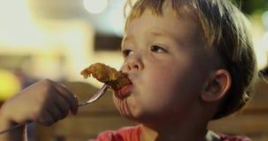 Garçon rêveur mangeant des pépites de poulet banque de vidéos