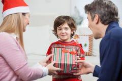 Garçon recevant le cadeau de Noël des parents photos libres de droits