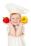 Garçon Red-haired dans le chapeau de cuisinier avec des légumes Photographie stock libre de droits