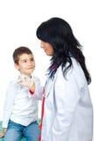 Garçon regardé curieusement le docteur Image libre de droits