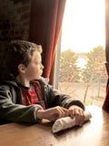 Garçon regardant à l'extérieur l'hublot Images libres de droits