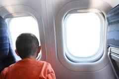 Garçon regardant à l'extérieur l'hublot d'avion à réaction Images libres de droits