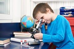 Garçon regardant dans le microscope Image stock