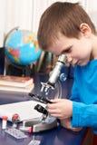 Garçon regardant dans le microscope Photographie stock