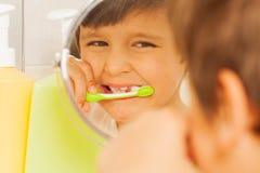 Garçon regardant en verre et apprenant à brosser des dents Photographie stock libre de droits