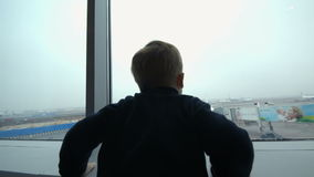 Garçon regardant l'avion de la fenêtre et l'imitant banque de vidéos
