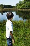 Garçon regardant l'eau images libres de droits