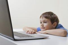 Garçon regardant l'ordinateur portable Éducation, étude, Internet, travail et concept social de media photo libre de droits